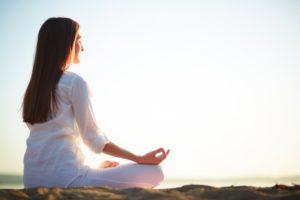 mujer-sentada-en-pose-de-yoga-en-la-playa_1098-1454